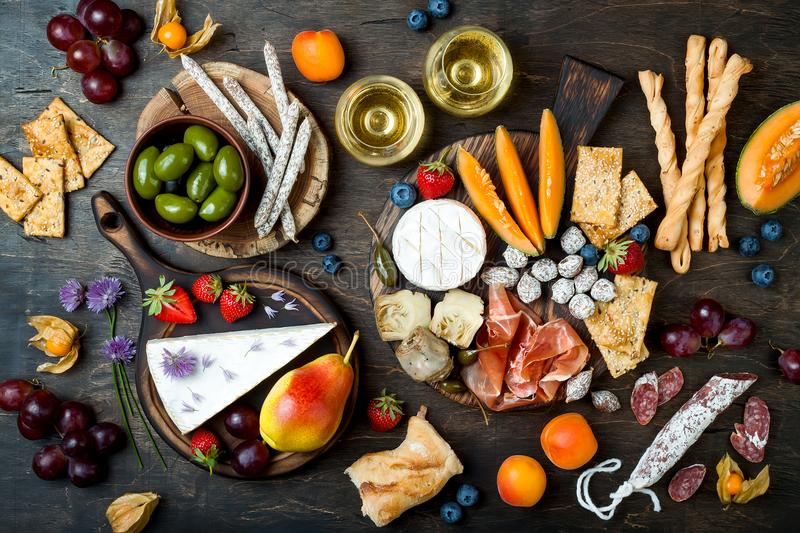 Appetizers table with italian antipasti snacks and wine in glasses. Cheese and charcuterie variety board over rustic wooden table stock image
