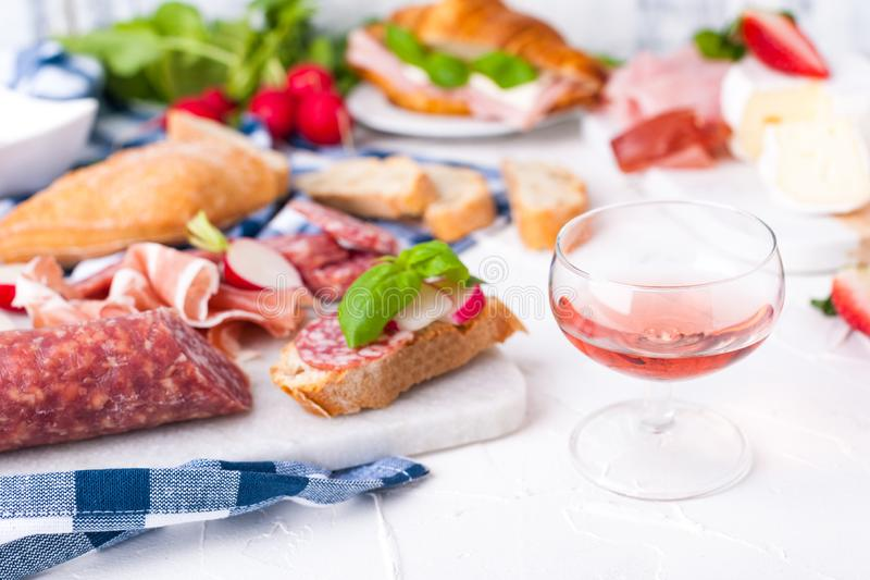 Appetizers table with italian antipasti snacks and wine in glasses. Salami and bruschetta with fresh vegetables on a white stock image