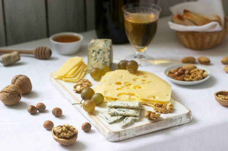 Appetizers of various types of cheese, grapes, nuts and honey, served with white and red wine. Rustic style royalty free stock photography