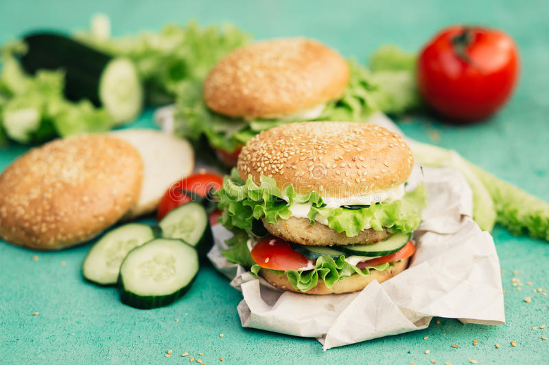 Appetizing burgers with ingredients. Unhealthy fastfood burgers with tomatoes, salad, cucumbers and chicken on turquoise background royalty free stock photography