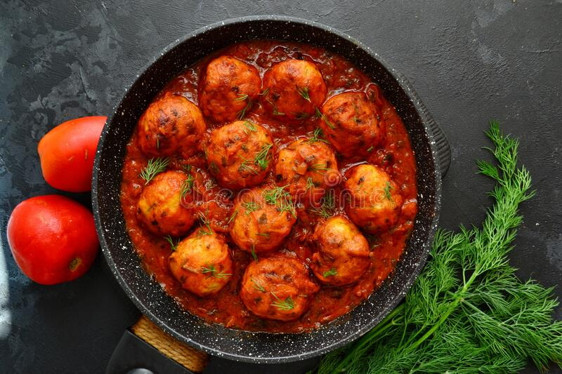 Appetizing chicken meatballs in tomato sauce. Meatballs in a pan on a dark table background. Chicken cutlets in tomato. Meat dish. Appetizing chicken meatballs stock image