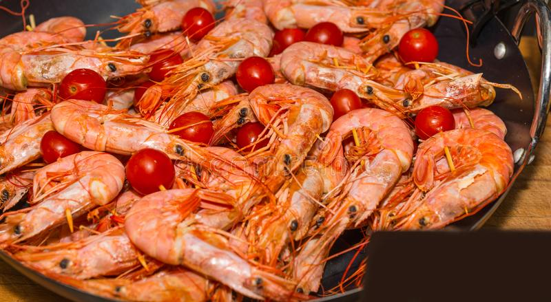 Appetizing cooked shrimps with tomatoes at food festival stock photography