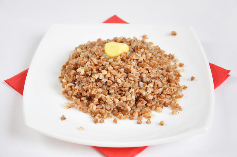 Appetizing crumbly buckwheat with butter. On white background royalty free stock image