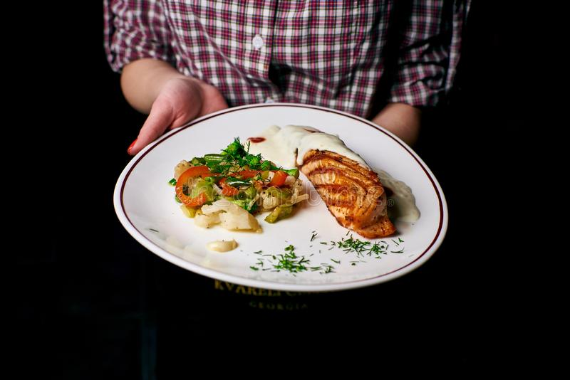 Appetizing dish on a white plate in the hands of the girl waiter, food stock photos