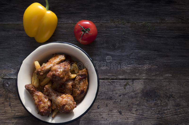 pieces of chicken wings and fried potatoes royalty free stock images