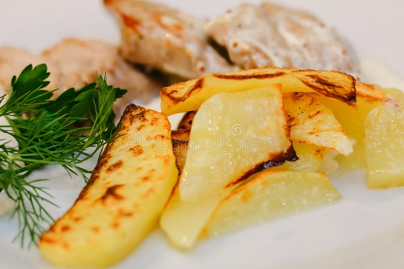 Appetizing fried potatoes with greens and pork meat stock photos