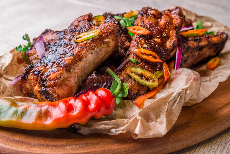 Appetizing grilled ribs decorated with hot pepper. Horizontal frame stock photos
