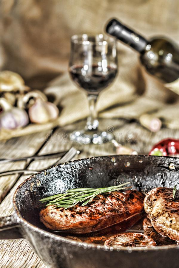 Appetizing grilled steak with rosemary and wine on the dining table stock photo