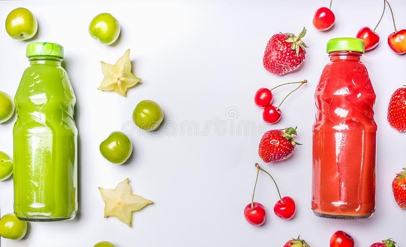 Appetizing healthy smoothies from carambola and green plum, strawberries and sweet cherries glass bottles on a white wooden rus. Appetizing healthy smoothies stock image
