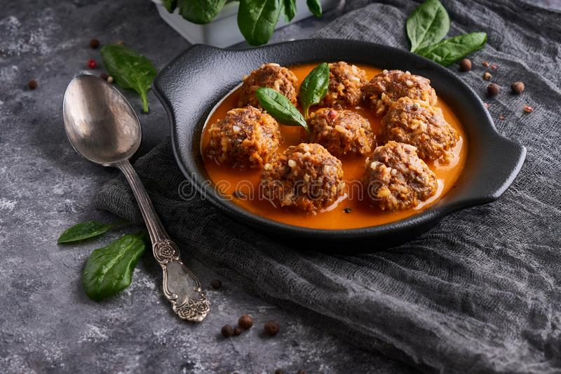 Appetizing homemade meatballs with tomato sauce and spinach in a plate on a dark background royalty free stock photography