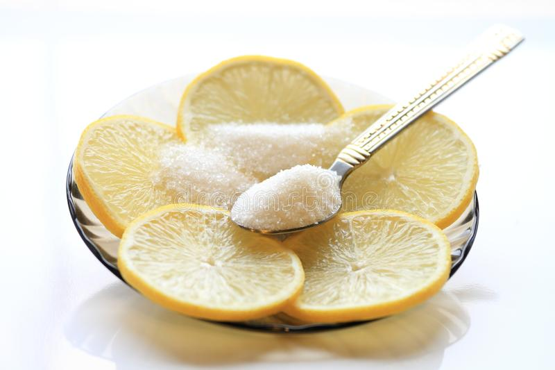 Appetizing lemon with slices and sugar, a teaspoon.  stock photography