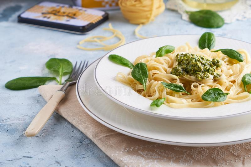 Appetizing pasta with sauce pesto and spinach in plate on light blue stone table.  royalty free stock image