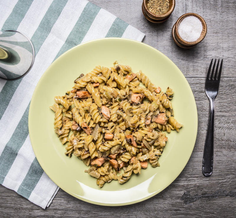 Appetizing pasta with smoked salmon, herbs and onions on a yellow plate on a striped napkin salt and pepper on wooden rustic. Appetizing pasta with smoked salmon royalty free stock image