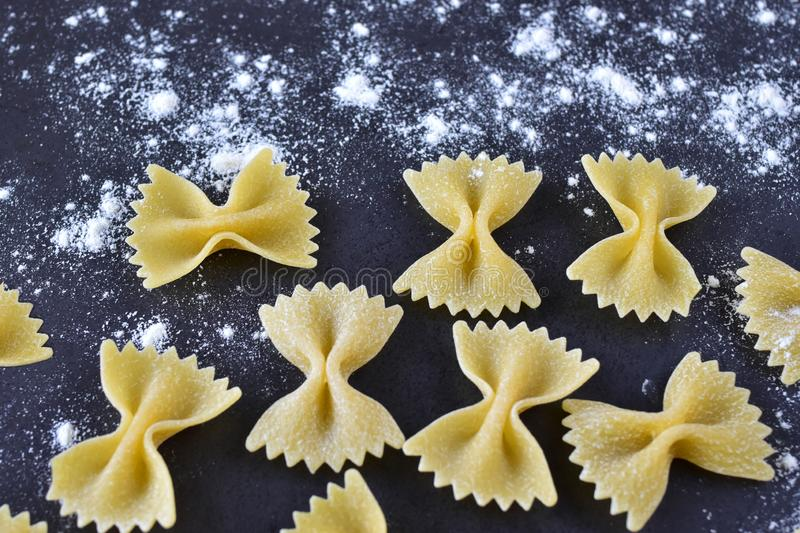 Appetizing pasta with your own hands - bows on a dark background, sprinkled with light wheat flour close-up royalty free stock photo