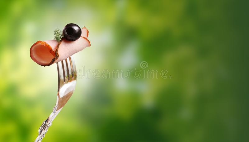 Appetizing piece of smoked meat on a fork against the blurred green foliage. stock image