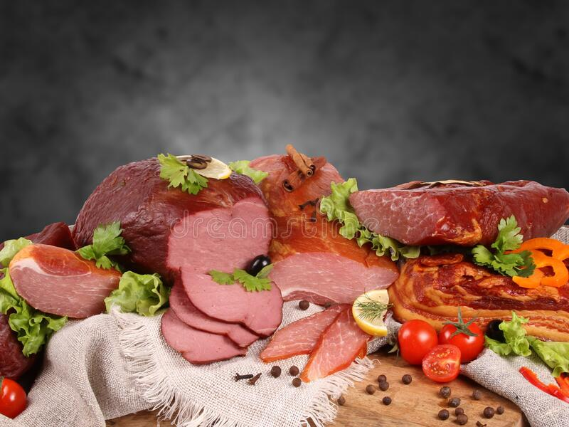 Appetizing piece of smoked meat with olive and a sprig of dill pinned on a fork against a black stone wall . stock image