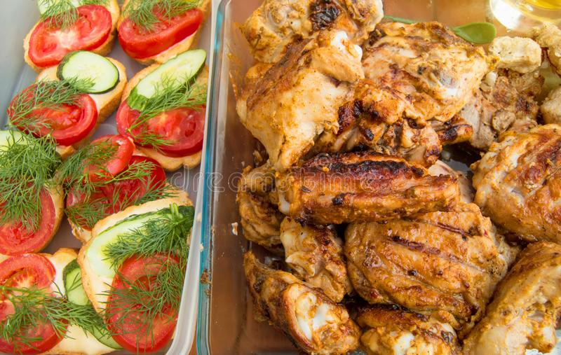 Appetizing pieces of grilled chicken and toast with tomatoes and cucumbers, delicious picnic food, sunlight, rays, food background royalty free stock photo