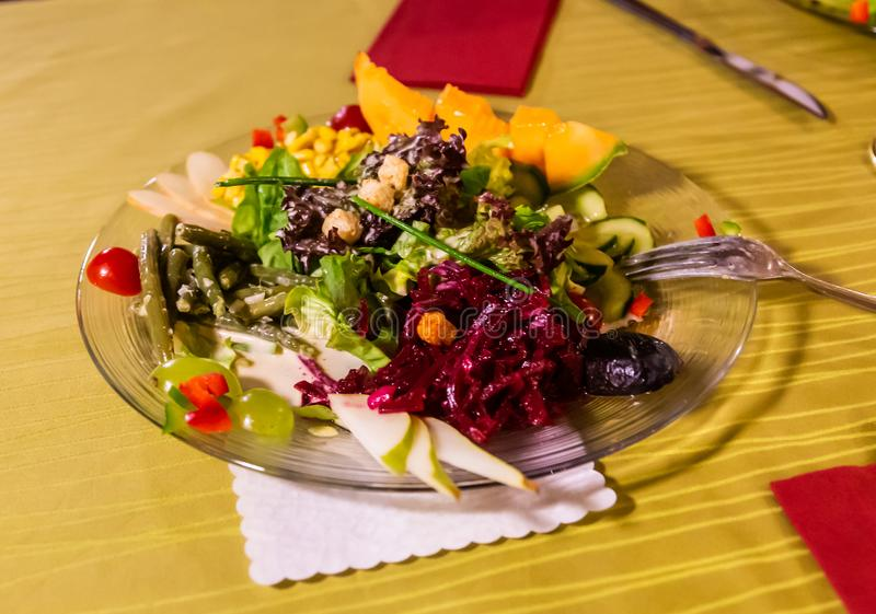 Appetizing salad of beets, mango, pears, asparagus and other vegetables and fruits royalty free stock photography