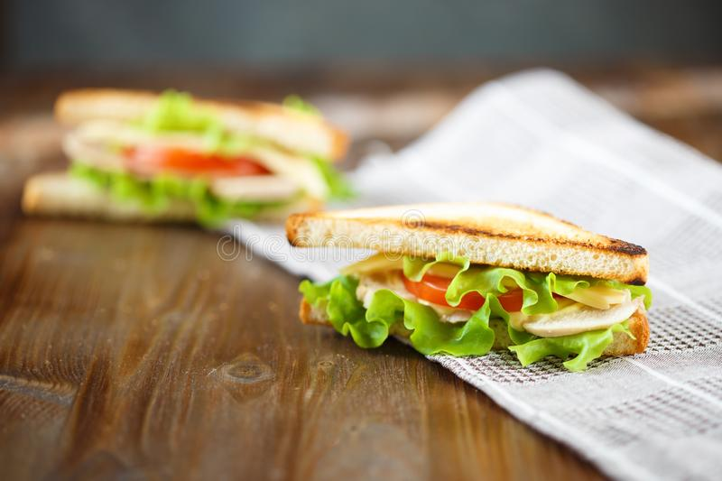 Appetizing sandwich with chicken, tomatoes, lettuce, cheese on a wooden plate on a dark background royalty free stock photography