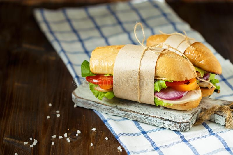 Appetizing sandwich from crispy bread with chicken, tomatoes, lettuce, cheese and spices on a dark wooden background. stock image