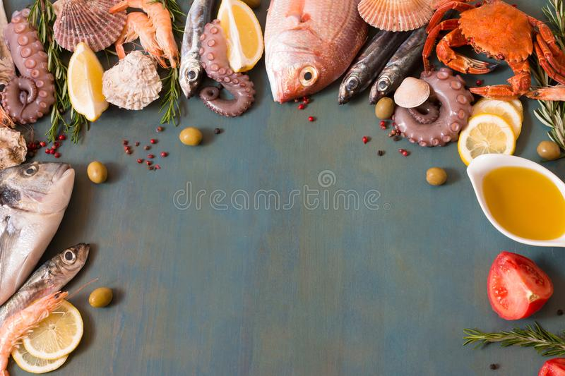Appetizing seafood and fish lay frame on blue background. stock photography