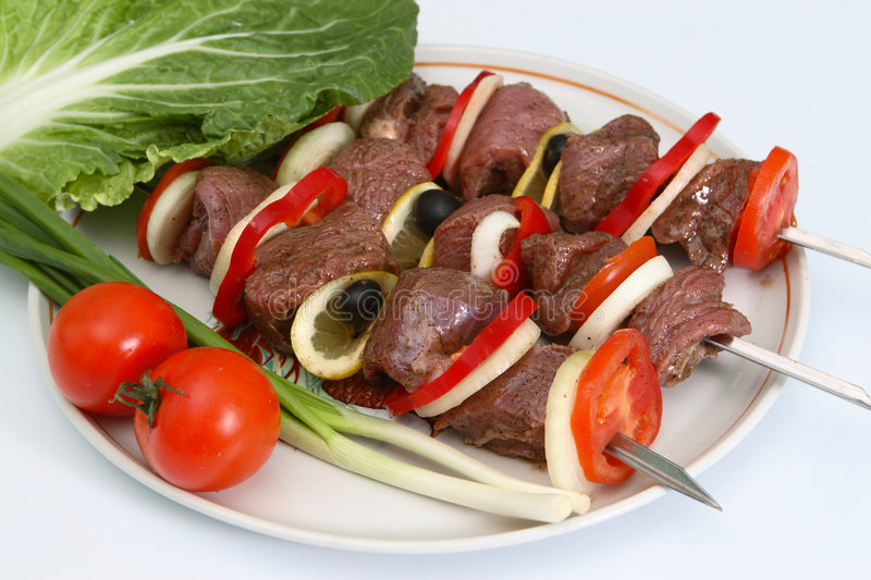 Appetizing shish kebab with vegetables and greens stock images