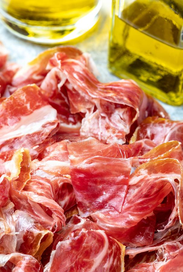 Appetizing slices Iberian ham in the foreground as a texture. Olive oil. Raw meat that becomes an article of haute cuisine and gastronomic luxury, through a royalty free stock images