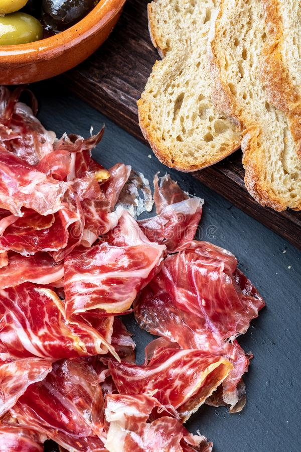 Appetizing slices Iberian ham in the foreground. Olive oil, bread, fresh tomato, olives. Black background. Rustic and homemade stock images