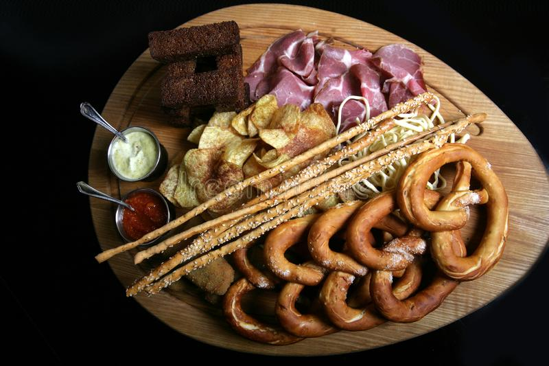 Appetizing snacks for beer - prosciutto, ham, homemade chips, grissini with sesame seeds, fried toast from dark bread and German stock image