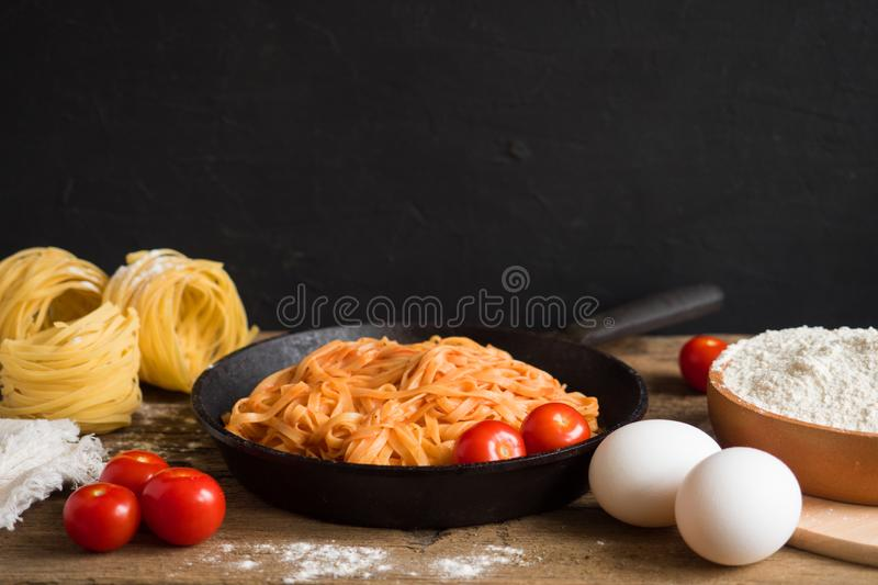 Appetizing traditional classic Italian pasta with tomato sauce and basil in a black frying pan on a wooden table. Space for text royalty free stock images