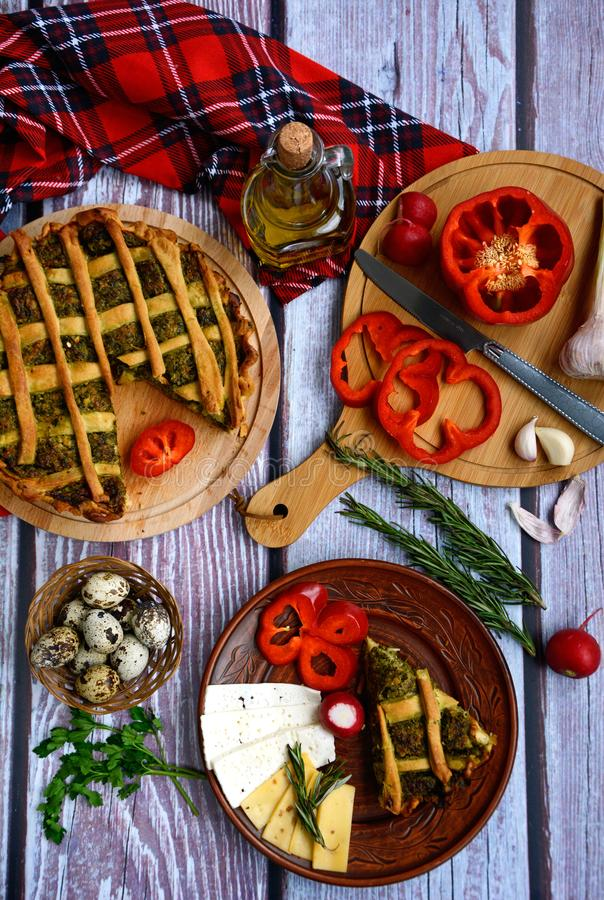 Appetizing vegetable pie, brown plate with a piece of pie, cheese and pepper, chopping board with sliced pepper, garlic, a bottle. Of olive oil, quail eggs and royalty free stock photo
