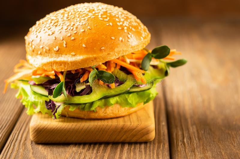 Appetizing veggie burger with fresh raw vegetables close-up on a dark wooden background. Healthy eating concept. stock image