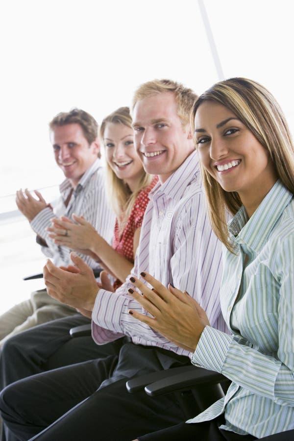 applådera businesspeople fyra som ler inomhus royaltyfria foton