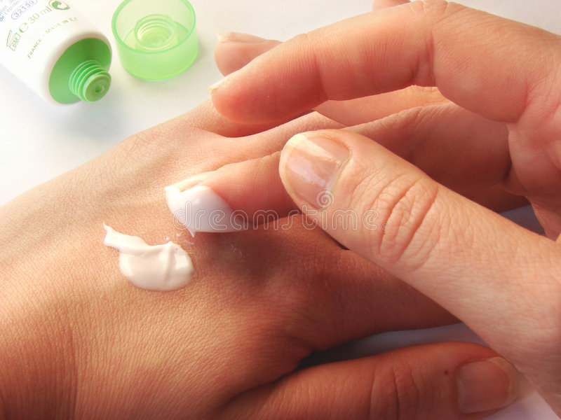 Applaing cream. Female hands applaing a cream close up stock photography