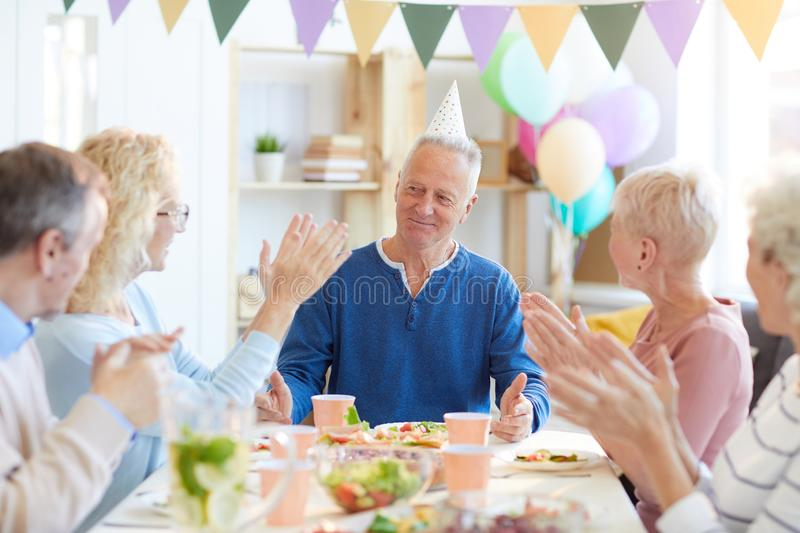 Applauding birthday man at dinner party stock photo