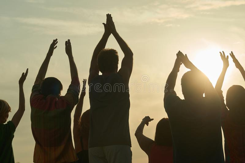 Applauding people silhouette. Rear back view handclapping family against morning sunrise stock image