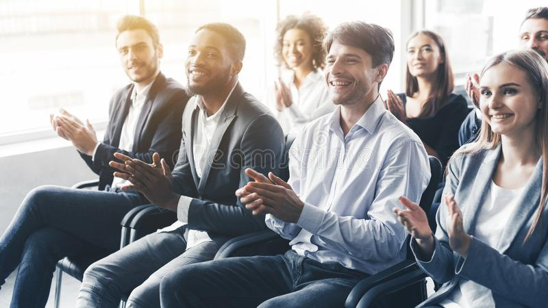 Applauding to speaker. Group of happy business people in conference hall. Applauding to speaker. Group of happy business people sitting in conference hall royalty free stock images