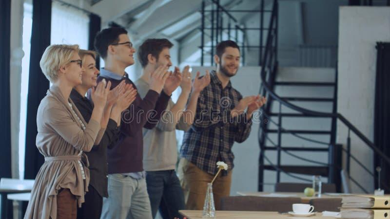 Applaus van opstarten van bedrijvenmensen in het bureau als team stock afbeeldingen