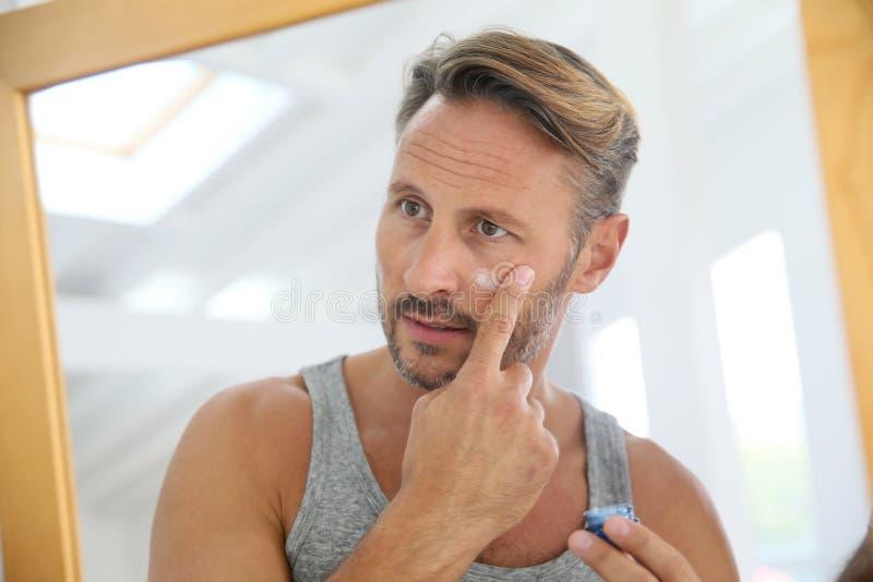 Applaying anti--åldras kräm för man på hans framsida royaltyfri fotografi