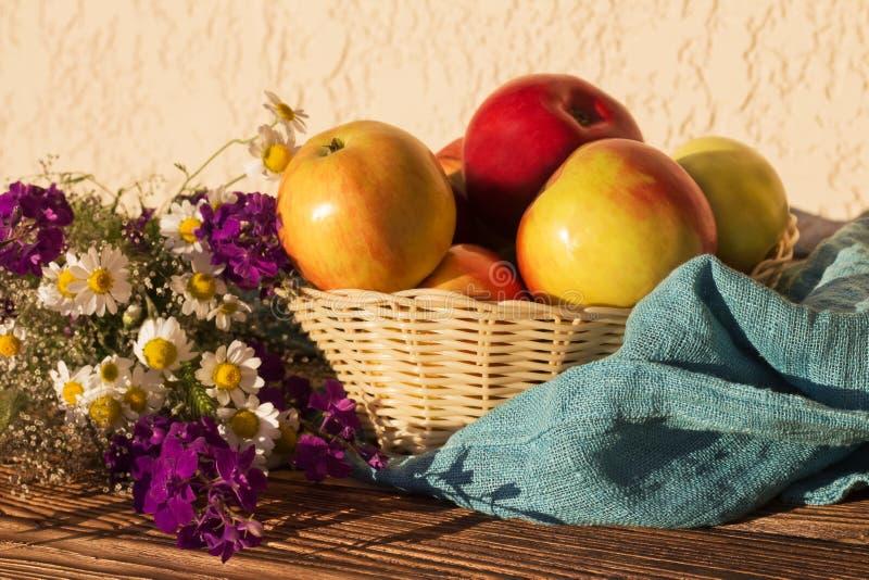 Apple äpplen i en vävd vas slösar buketten för lösa blommor för handduken på en trätabellnärbild royaltyfria foton