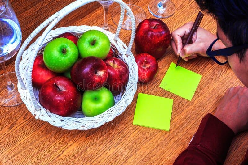 Apple är i korg och på den wood tabellen En man skriver den pappers- korta anmärkningen, och han är kläderexponeringsglas arkivbild