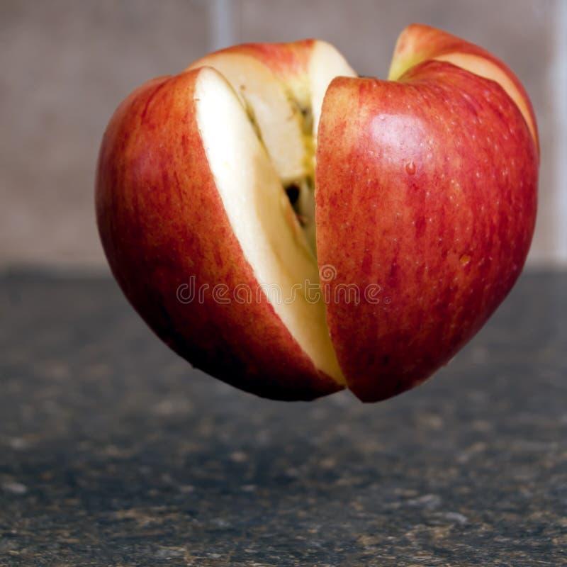 Apple étant coupé dedans à moitié photographie stock