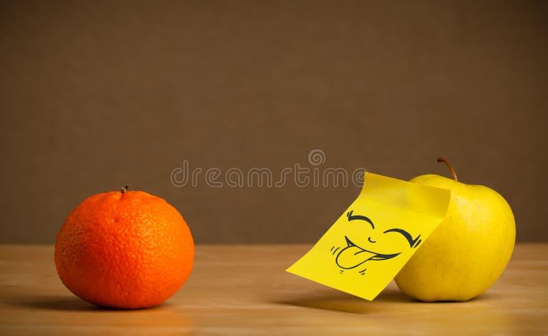 Apple με post-it τη σημείωση που κολλά έξω τη γλώσσα στο πορτοκάλι στοκ φωτογραφίες με δικαίωμα ελεύθερης χρήσης