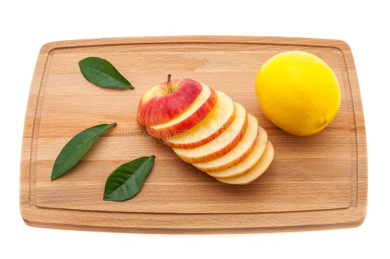 Apple νόστιμη, φρέσκια και juicy με τα πράσινα φύλλα και το λεμόνι σε έναν τέμνοντα πίνακα φιαγμένο από ξύλο στοκ φωτογραφία
