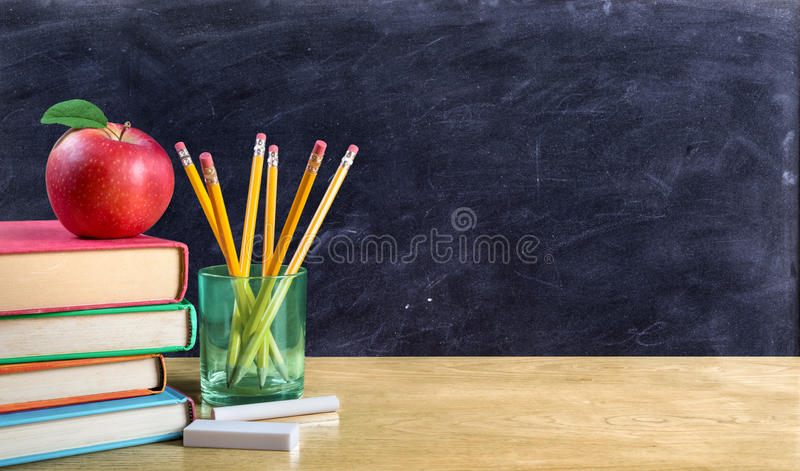 Apple στα βιβλία με τα μολύβια και τον κενό πίνακα στοκ εικόνα