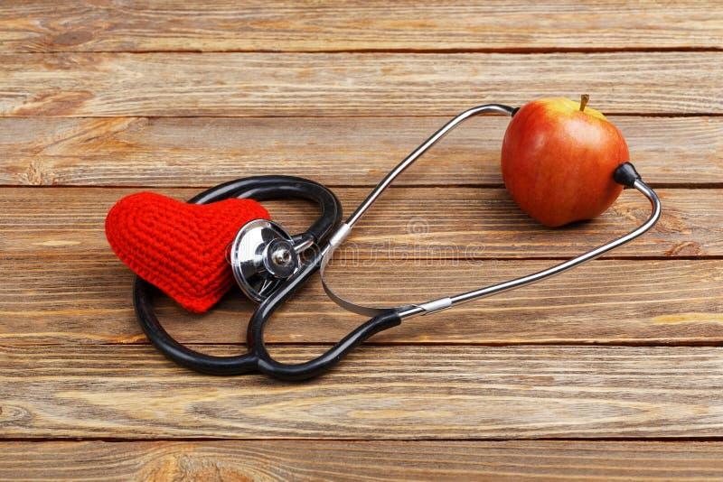 Apple, στηθοσκόπιο και καρδιά στο ξύλινο υπόβαθρο στοκ φωτογραφίες με δικαίωμα ελεύθερης χρήσης