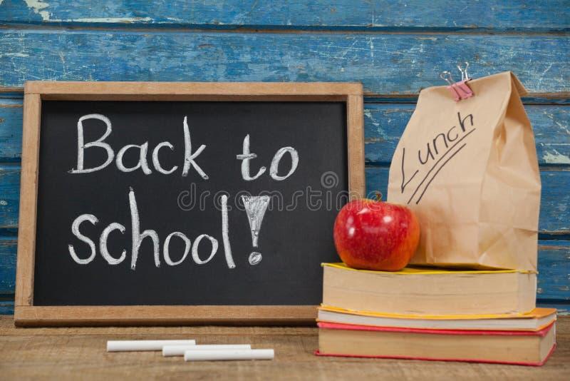Apple, τσάντα μεσημεριανού γεύματος, βιβλία και πλάκα με πίσω στο σχολικό κείμενο στοκ εικόνα