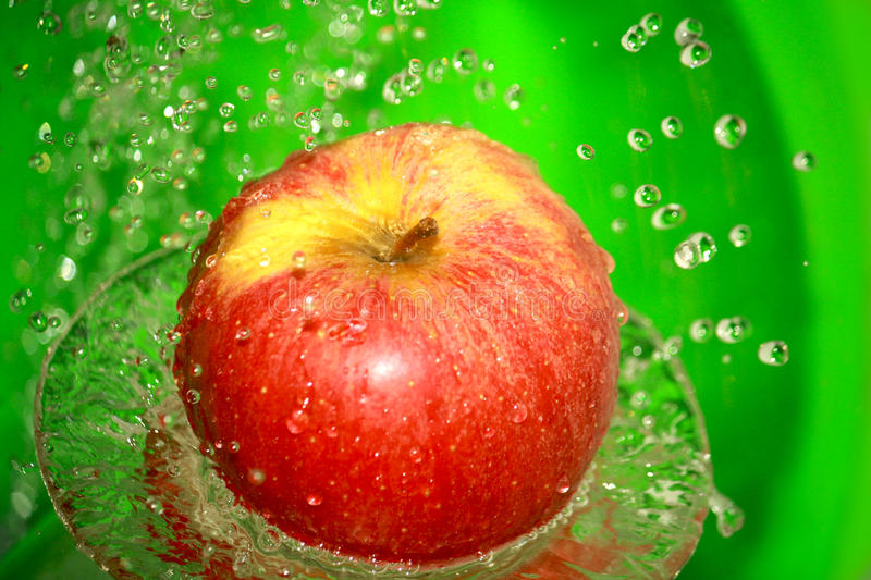 Apple. The red apple in the water with many drops royalty free stock photography