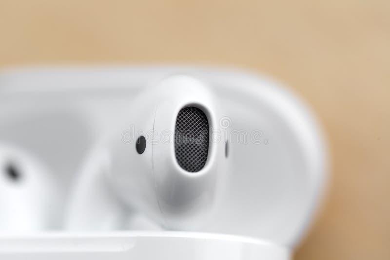 Apple Airpods i ett laddande fall på en träyttersida royaltyfria bilder