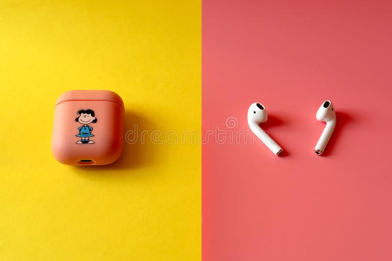 Apple AirPods wireless headphone with charging box on a multi-colored background pink and yellow. Use with Iphone, Ipad or Mac. Apple AirPods wireless headphone royalty free stock photos
